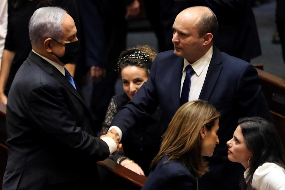 Benjamin Netanyahu shakes hands with the man who has replaced him as Israel Prime Minister, Naftali Bennett, following the vote on the new coalition at the Knesset, Israel's parliament (REUTERS)