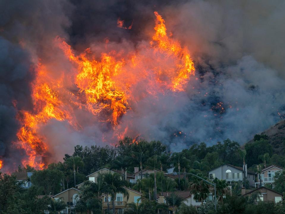 Flames rise near homes during the Blue Ridge wildfire on October 27, 2020 in Chino Hills, California. A new poll has found that the majority of Americans think we are running out of time to save the planet from the climate crisis (Getty Images)