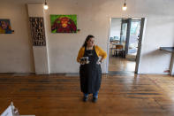 Cafe owner Maria Iatrou stands at her empty coffee shop in Melbourne, Monday, July 6, 2020. As Australia is emerging from pandemic restrictions, the Victoria state capital Melbourne is buckling down with more extreme and divisive measures that are causing anger and igniting arguments over who is to blame as the disease spreads again at an alarming rate. (AP Photo/Andy Brownbill)