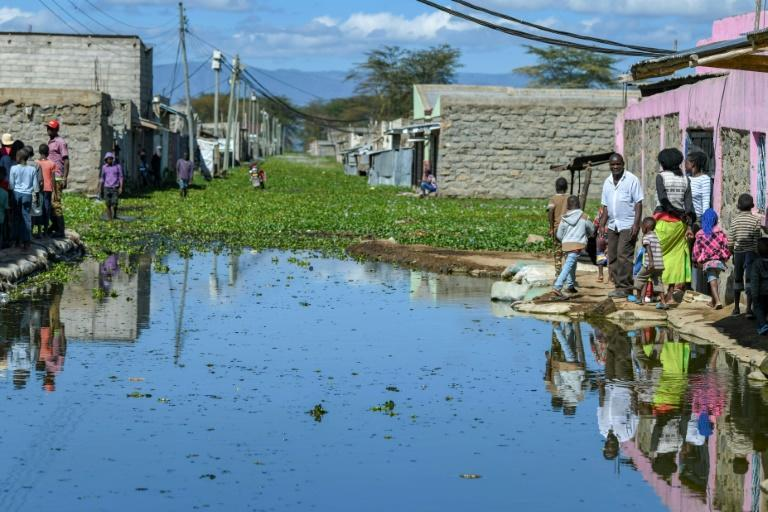 Residents of Kihoto estate on the shores of Lake Naivasha stand on elevated pavements outside their homes after the lake inundated buildings and infrastructure
