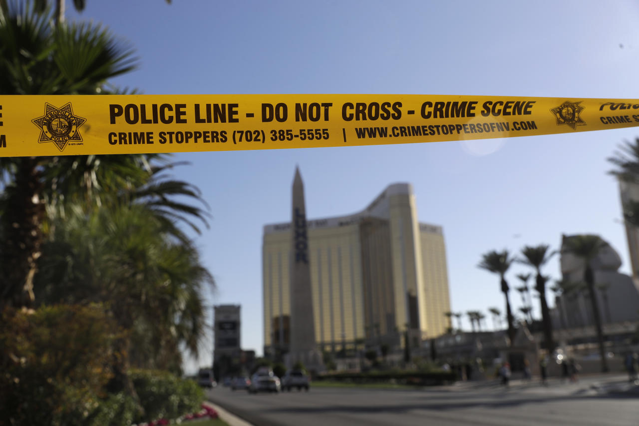FILE - In this Oct. 4, 2017 file photo, part of Reno Ave. near South Las Vegas Blvd is blocked with police tape in the aftermath of a mass shooting in Las Vegas. Police in Las Vegas released more body-worn camera videos of officers responding to the deadliest mass shooting in the nation's modern history nearly a year ago. Amid the 42 clips made public Wednesday, Sept. 19, 2018, displaced hotel guests are seen sleeping in hotel hallways, officers check Las Vegas Strip convenience stores and an argumentative man is arrested after insisting he was going to walk toward the shooting scene. (AP Photo/Marcio Jose Sanchez, File)