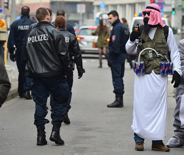 Police officers patrol past a man dressed up ready for the carnival parade in Braunschweig (AFP Photo/Julian Stratenschulte)