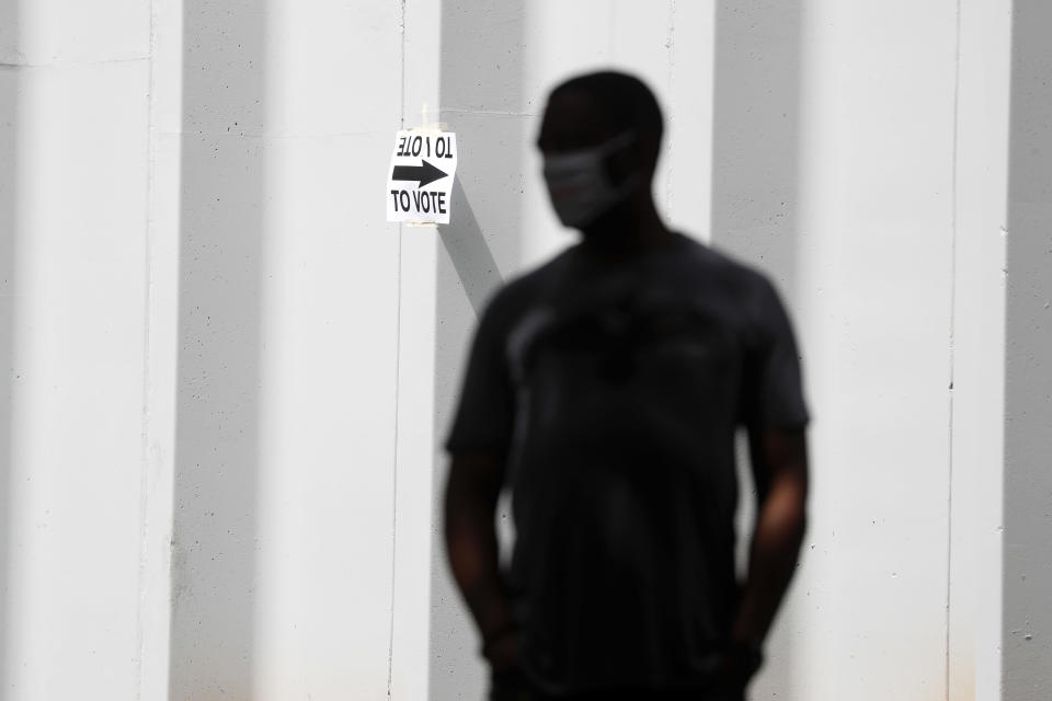 A man waits to vote at Central Park, Tuesday, June 9, 2020, in Atlanta. Voters reported wait times of three hours. (AP Photo/John Bazemore)