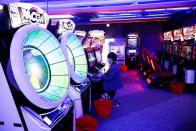 A man wearing a mask enjoys a game at a video arcade amid the coronavirus disease (COVID-19) pandemic in Seoul