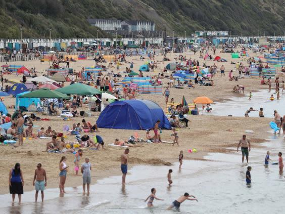 People enjoy the hot weather at Boscombe beach in Dorset (PA)