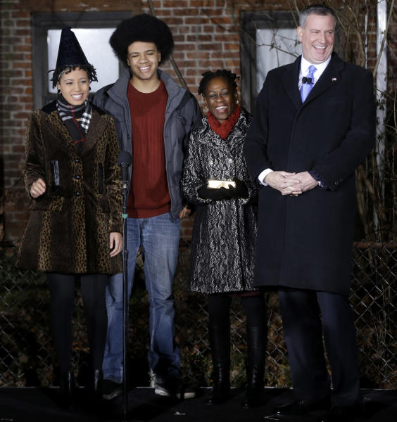 Bill de Blasio, right, laughs with his family, Chiara de Blasio, left, Dante de Blasio, second from left, and Chirlane McCray before being sworn in as the mayor of New York City at the start of the new year, Wednesday, Jan. 1, 2014 in New York. De Blasio took the oath of office moments after midnight at his home in Park Slope, Brooklyn. His inauguration will be celebrated at noon Wednesday on the steps of City Hall when he takes the oath again, which will be administered by former President Bill Clinton. (AP Photo/Seth Wenig, Pool)