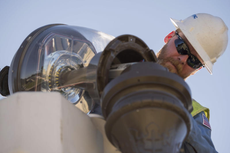 In this July 18, 2019 photo provided by the U.S. Navy, Tim Goodwin, a high-voltage electrician with Naval Facilities Engineering Command (NAVFAC), repairs a street lamp on Naval Air Weapons Station China Lake, Calif. The base sustained heavy earthquake damage that experts estimate will cost over $5 billion to repair. (Mass Communication Specialist 3rd Class Jeffery L. Southerland/U.S. Navy via AP)