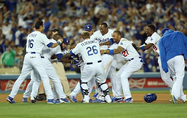 LOS ANGELES, CA - APRIL 08: (L-R) Andre Ethier #16, Yasiel Puig #66, Scott Van Slyke #33, Tim Federowicz #26, Justin Turner #10, Juan Uribe #5 and Matt Kemp #27 of the Los Angeles Dodgers mob teammate Carl Crawford #3 after Crawford drove in the game-winning run against pitcher Phil Coke #40 of the Detroit Tigers (not in photo) as teammate Dee Gordon #9 joins the celebration after their MLB game at Dodger Stadium on April 8, 2014 in Los Angeles, California. The Dodgers defeated the Tigers 3-2 in 10 innings. (Photo by Victor Decolongon/Getty Images)