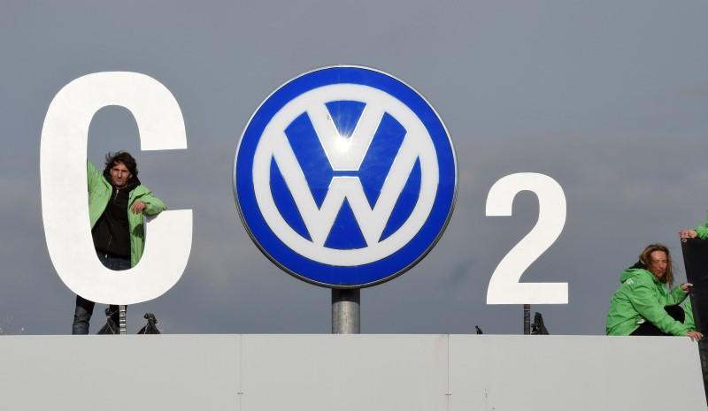 """Greenpeace activists demonstrate as they stand on top of Volkswagen's """"Sandkamp"""" gate in Wolfsburg"""