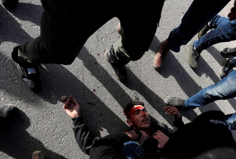 A wounded Palestinian demonstrator is helped during a protest against Israeli settlements, near the town of Beita in the Israeli-occupied West Bank