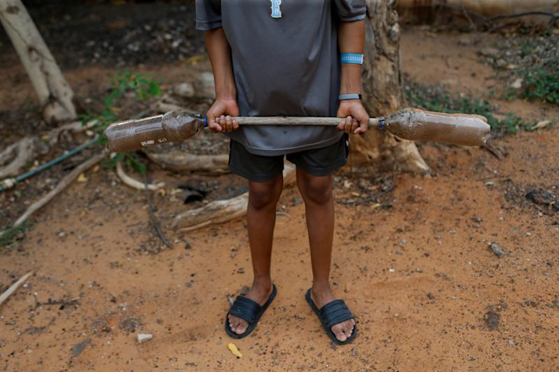 Baseball little league player Adrian Salcedo, 13, trains with homemade weights at his home in Maracaibo, Venezuela. (Photo: Manaure Quintero/Reuters)