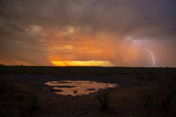 As the sun begins to set at the Moringa water hole in Etosha National Park, a thunderstorm moves into the area. Thunder and lightning pass very close to the surface, shaking the ground. (Photo: Gordon Donovan/Yahoo News)