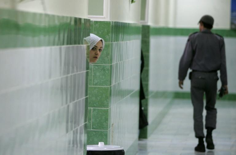 A prisoner peeks out at the hallway at Tehran's Evin prison in June 2006