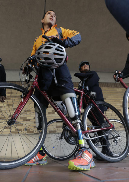 Cyclist Carlos Gutierrez, a double amputee, stands with his bike, Thursday, Nov. 7, 2013, in San Antonio. Gutierrez, a Mexican asylum seeker who fled to the U.S. after extortionists cut his legs off for not paying the extortion fees, is riding his bike from El Paso, Texas to Austin, Texas, to raise awareness on the situation of political asylum seekers. (AP Photo/Eric Gay)