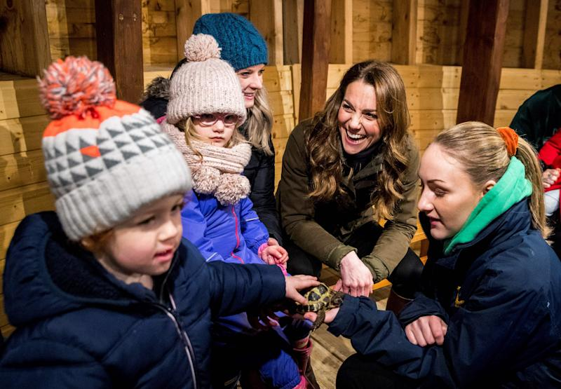 Britain's Catherine, Duchess of Cambridge (2R) reacts as she helps children bottle-feed a lamb during her visit to Ark Open Farm near Belfast on February 12, 2020, as part of her tour of the UK to promote her landmark survey on the early years, '5 Big Questions on the Under-Fives'. (Photo by Liam McBurney / POOL / AFP) (Photo by LIAM MCBURNEY/POOL/AFP via Getty Images)