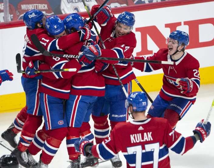 Montreal Canadiens right wing Tyler Toffoli (73) is mobbed by teammates after scoring the winning goal following overtime NHL Stanley Cup playoff hockey action against the Winnipeg Jets in Montreal, Monday, June 7, 2021. (Ryan Remiorz/The Canadian Press via AP)