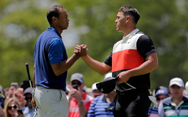 Tiger Woods, left, and Brooks Koepka shake hands after finishing the first round of the PGA Championship on Thursday at Bethpage Black in New York. (AP/Seth Wenig)