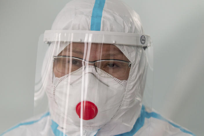 """Dr. Tatyana Symbelova speaks during a daily examination of patients suspected of having coronavirus in the red zone of the hospital in Ulan-Ude, the regional capital of Buryatia, a region near the Russia-Mongolia border, Russia, Friday, Nov. 20, 2020. Symbelova told the AP that as the number of patients rose, her hospital kept adding beds — """"in the corridor, in the outpatient ward next door"""" — but """"the situation, still, grew worse and worse."""" (AP Photo/Anna Ogorodnik)"""
