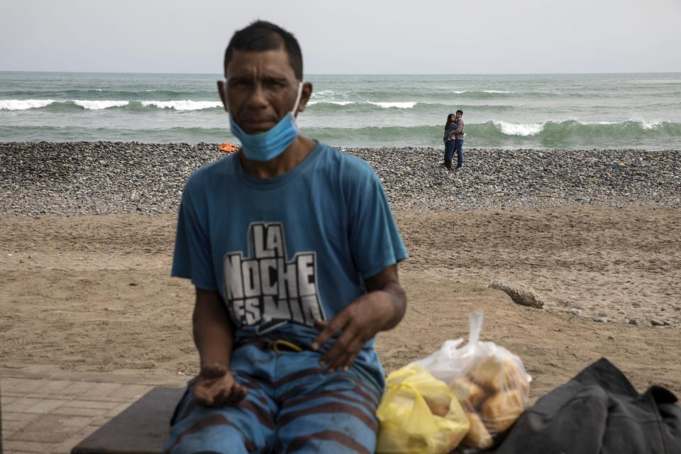 A couple embraces, background, while homeless Gustavo Castaneda rests on a bench near the Pacific Ocean on the coast of Lima, Peru, Friday, June 26, 2020, amid the coronavirus pandemic. (AP Photo/Rodrigo Abd)