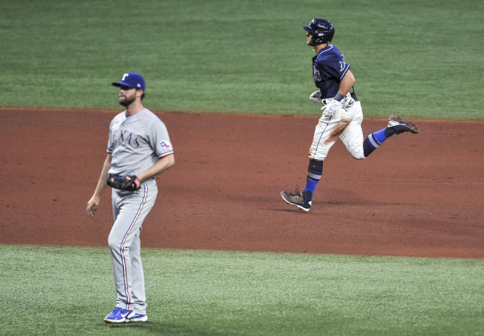 Tampa Bay Rays' Mike Brosseau, right, circles the bases after hitting a two-run home run off Texas Rangers' Jordan Lyles during the fourth inning of a baseball game Thursday, April 15, 2021, in St. Petersburg, Fla. (AP Photo/Steve Nesius)