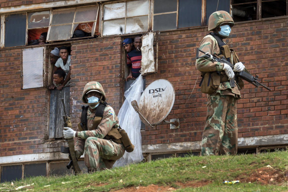"""South African National Defense Forces patrol the Men's Hostel in the densely populated Alexandra township east of Johannesburg, Saturday, March 28, 2020, enforcing a strict lockdown in an effort to control the spread of the coronavirus. Photographer Jerome Delay said the scene reminded him of South Africa before apartheid ended in 1994, with the army raiding the hostel not looking for guns but enforcing a strict lockdown that included a ban on the use of cigarettes and alcohol. He says he still hears the men, packed six to a room, shouting down the halls: """"If we can't go out and can't work, we can't eat."""" (AP Photo/Jerome Delay)"""