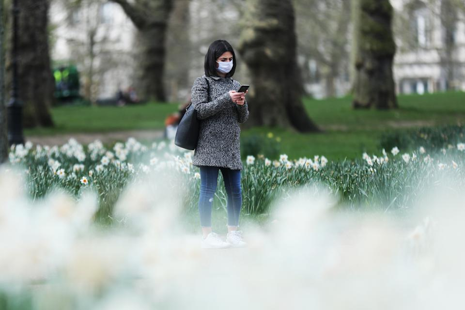 A woman wearing a face mask in Green Park, London, as the UK's coronavirus death toll rose to 35 with a total of 1,372 positive tests for coronavirus in the UK as of 9am on Sunday.