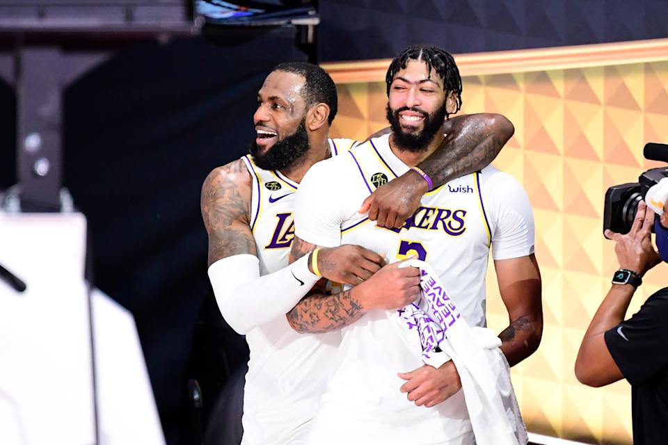 LeBron James #23 of the Los Angeles Lakers and Anthony Davis #3 of the Los Angeles Lakers react after winning the 2020 NBA Championship in Game Six of the 2020 NBA Finals.