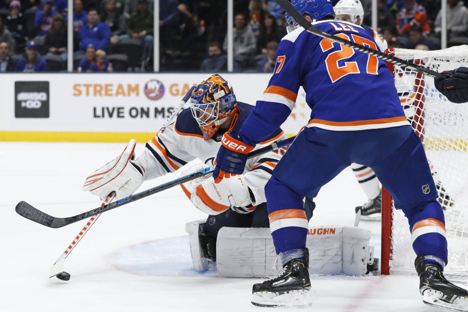 Edmonton Oilers goaltender Mikko Koskinen (19) corrals the puck in front of New York Islanders left wing Anders Lee (27) during the second period of an NHL hockey game Tuesday, Oct. 8, 2019, in Uniondale, N.Y. (AP Photo/Kathy Willens)