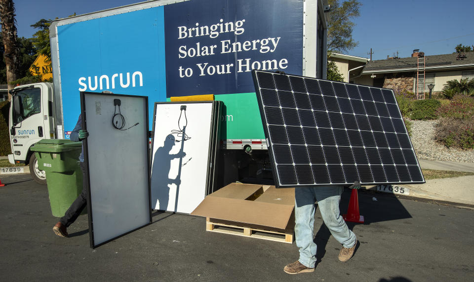 GRANADA HILLS, CA - JANUARY 04, 2020: Aaron Newsom, left, an installer for the solar company, Sunrun, and Tim McKibben, a senior installer, prepare solar panels to be installed on the roof of a home in Granada Hills.  (Mel Melcon / Los Angeles Times via Getty Images)