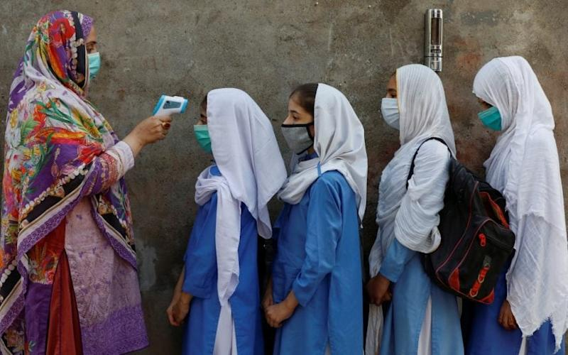 Students wear protective masks as they have their temperature checked before entering a class, after government allowed reopening of schools from grade six to eight amid the coronavirus disease (COVID-19) pandemic, in Peshawar, Pakistan - Fayaz Aziz/REUTERS