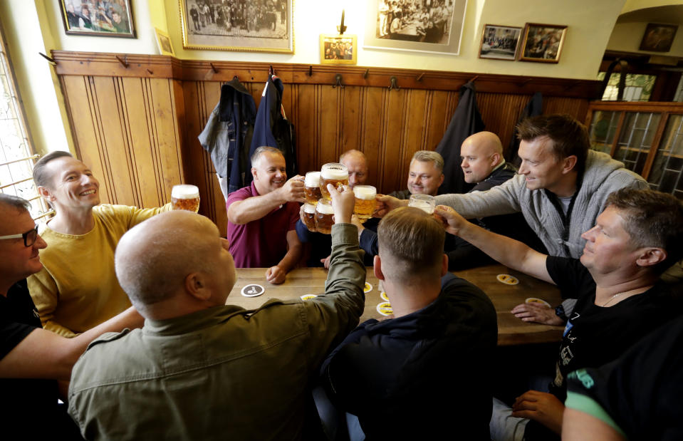 Customers cheer with beer as a traditional beer pub opens in Prague, Czech Republic, Monday, May 25, 2020. The bars, restaurants and cafes are returning to full service in the Czech Republic as the government is taking further steps to ease its restrictive measures adopted to contain the coronavirus pandemic. (AP Photo/Petr David Josek)