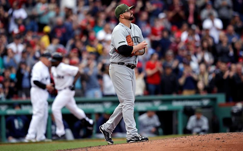 Seattle Mariners starting pitcher Rob Whalen prepares a fresh baseball as he walks back to the mound while Boston Red Sox's Jackie Bradley Jr. rounds the bases on his two-run home run during the sixth inning of a baseball game at Fenway Park in Boston, Saturday, May 27, 2017. (AP Photo/Charles Krupa)