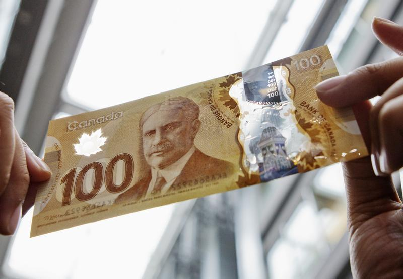 A man holds the new Canadian 100 dollar bill made of polymer in Toronto