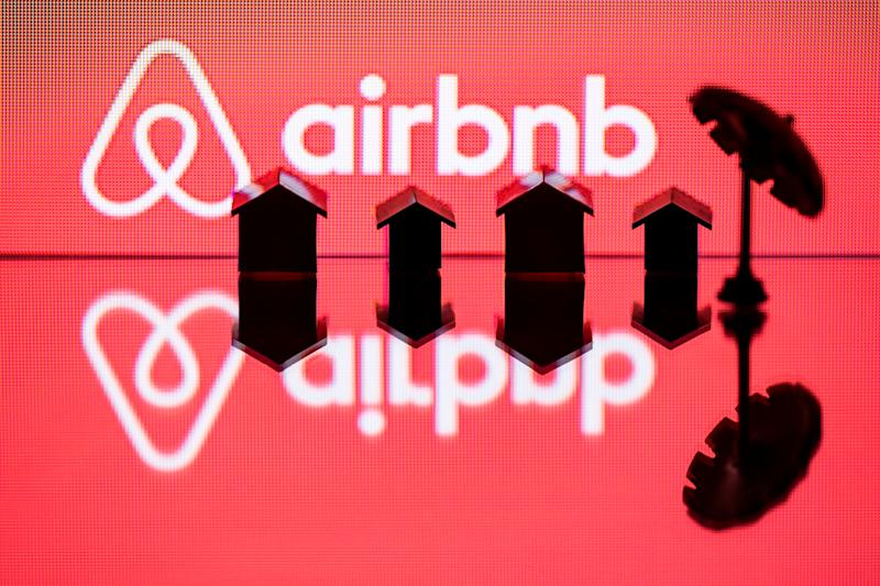 This illustration picture taken in Paris on August 29, 2018, shows a toy umbella and houses next to the logo of rental website Airbnb. (Photo by JOEL SAGET / AFP) (Photo credit should read JOEL SAGET/AFP/Getty Images)
