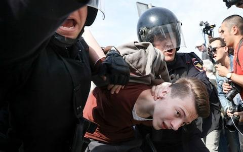 Russian police detain a protester at a demonstration against President Vladimir Putin in Pushkin Square in Moscow - Credit: AP