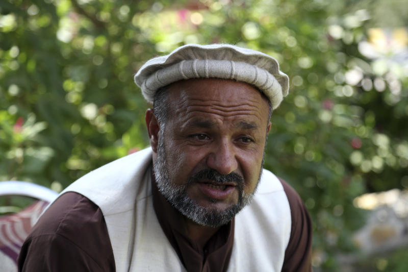 In this Tuesday, Oct. 1, 2019, photo, Aziz Rahman a village elder, who had contracted the farmers to harvest the pine nuts, speaks during an interview to the Associated Press in Jalalabad city east of Kabul, Afghanistan.  Anger is mounting over the increasing numbers of civilians dying in misdirected US aerial strikes and heavy- handed tactics of CIA-trained Afghan force. Some Afghans calling for Americans to be tried in Afghan courts. (AP Photo/Rahmat Gul)