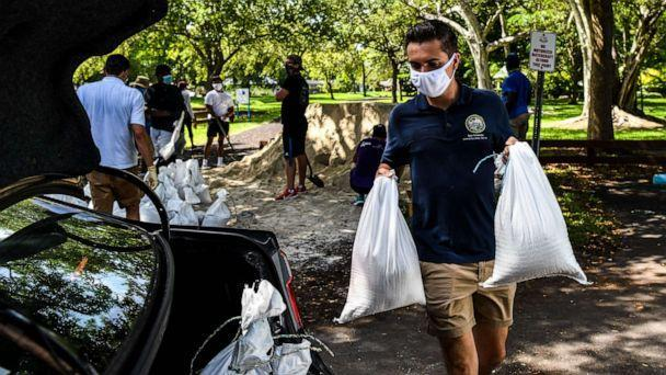 PHOTO: Legislative Assistant Ryan Fernandez, puts sand bags in a resident's car trunk in Palmetto Bay near Miami, on July 31, 2020, as Floridians prepare for Hurricane Isaias while a State of Emergency has been declared for 19 Counties. (Chandan Khanna/AFP via Getty Images)