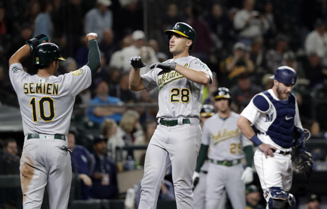 Oakland Athletics' Matt Olson (28) is congratulated by Marcus Semien (10) on his grand slam as Seattle Mariners catcher Chris Herrmann looks down during the fifth inning of a baseball game Wednesday, Sept. 26, 2018, in Seattle. (AP Photo/Elaine Thompson)
