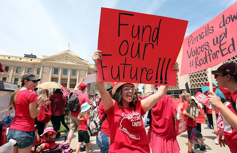 An Arizona teacher holds up a sign in front of the state Capitol during a rally on April 26. Legislation signed by the governor Thursday meets some of their demands. (Ralph Freso via Getty Images)