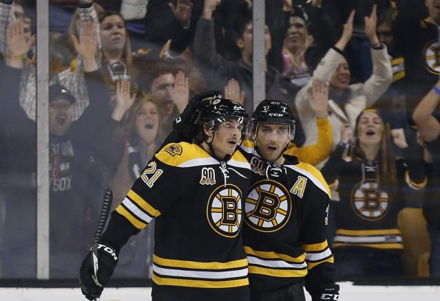 Boston Bruins' Patrice Bergeron, right, celebrates his open-net goal with teammate Loui Eriksson (21), of Sweden, in the third period of an NHL hockey game against the Toronto Maple Leafs in Boston, Saturday, Nov. 9, 2013. The Bruins won 3-1. (AP Photo/Michael Dwyer)