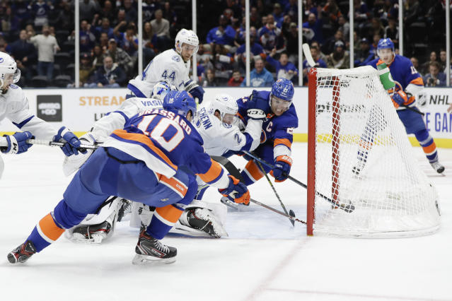 New York Islanders' Anders Lee (27) and Derick Brassard (10) and Tampa Bay Lightning's Luke Schenn (2) reach for a puck shot by Islanders' Mathew Barzal (13) for a goal during the second period of an NHL hockey game Friday, Nov. 1, 2019, in Uniondale, N.Y. (AP Photo/Frank Franklin II)
