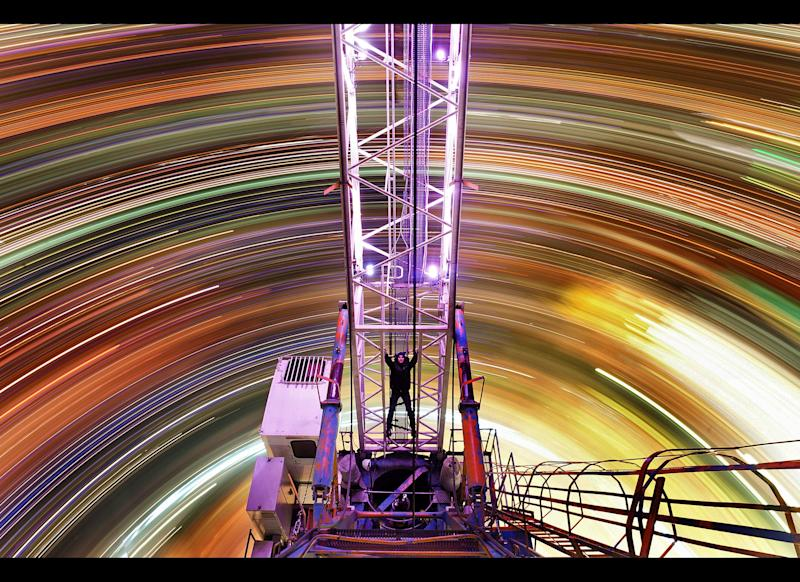 Swirling colors of city lights from a 900ft crane fill the Moscow skyline. Photographer D. Chistoprudov boards the crane, which is being used to build a skyscraper called Federation, and takes pictures over a period of two hours. Chistoprudov, 28, starts taking the swirling snaps around 1am and battles freezing weather to remain completely still so not to ruin the careful process. (Caters News / ZUMA Press)