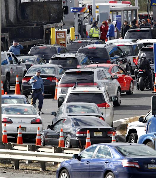 New Jersey state troopers keep order as motorist line up to purchase gasoline at the Thomas A. Edison service area on the New Jersey Turnpike Saturday, Nov. 3, 2012, near Woodbridge, N.J., before a noon switch to a gas rationing system in 12 counties ordered by Gov. Chris Christie. Drivers with license plates ending in an even number will be allowed to buy gas on even-numbered days, and those with plates ending in an odd number can make gas purchases on odd-numbered days. Christie says it will help ease fuel shortages and extended lines for gasoline that have occurred since Superstorm Sandy decimated the coast. (AP Photo/Mel Evans)