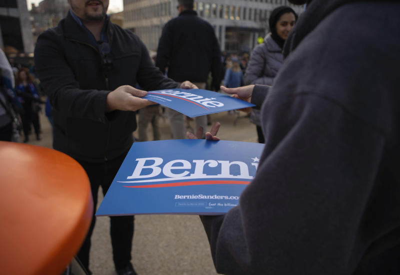 Volunteers hand out signs at a rally for Bernie Sanders at Calder Plaza in Grand Rapids, Michigan on Sunday, March 8, 2020. Michigan's presidential primary is Tuesday.(Anntaninna Biondo/The Grand Rapids Press via AP)