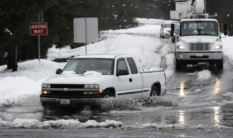 A truck drives through standing water on a highway offramp, Tuesday, Feb. 12, 2019, in Olympia, Wash. As heavy snow turned into rain Tuesday in the Pacific Northwest, crews worked to clear drains and roadways as concerns about flooding and drainage increased. February has been the snowiest month for the area in more than 50 years, and the National Weather Service issued a flood watch for northwest Oregon and parts of Washington through Wednesday morning. (AP Photo/Ted S. Warren)