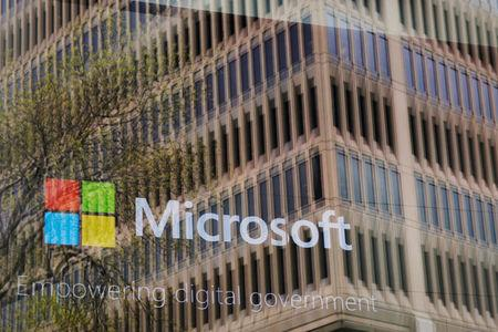 FILE PHOTO: An promotional video plays behind a window reflecting a nearby building at the Microsoft office in Cambridge, Massachusetts, U.S. on May 15, 2017. REUTERS/Brian Snyder/File Photo