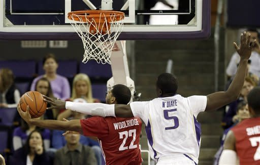 Washington's Aziz N'Diaye (5) tries to block a shot by Washington State's Royce Woolridge (22) in the first half of an NCAA college basketball game on Sunday, March 3, 2013, in Seattle. (AP Photo/Ted S. Warren)