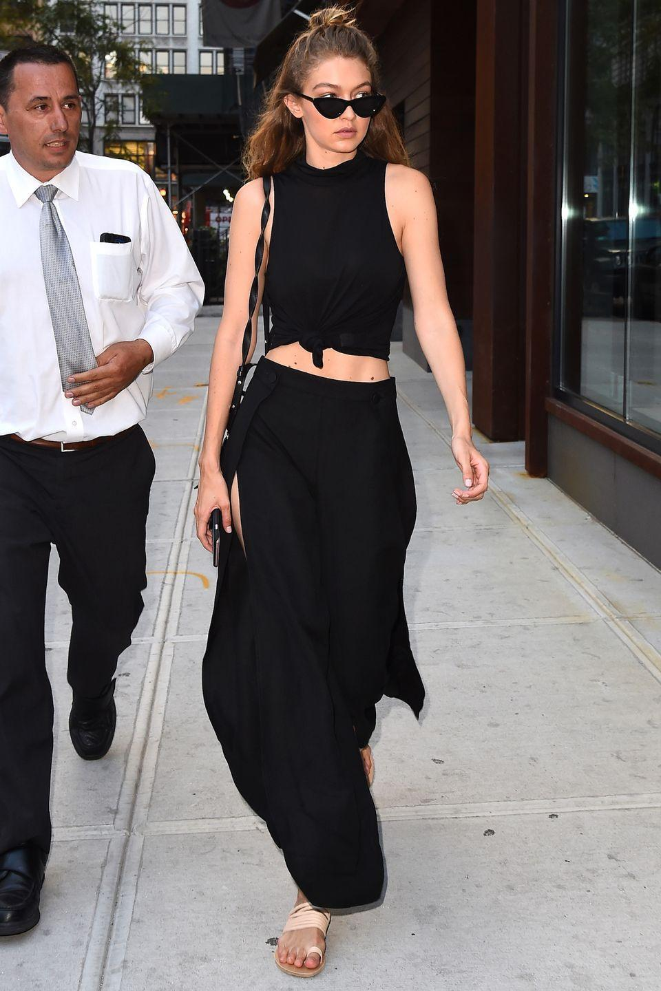 <p>In a knotted black crop top, thigh-high slit trousers, strappy nude sandals and black cat-eyed sunglasses in New York City.</p>