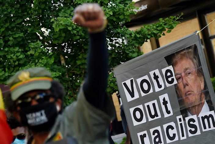 A demonstrator raises his fist in front of a sign calling to vote out racism with a picture of President Donald Trump during a peaceful protest against police brutality and the death of George Floyd, on June 7, 2020 in Washington, DC. (Olivier Douliery/AFP via Getty Images)