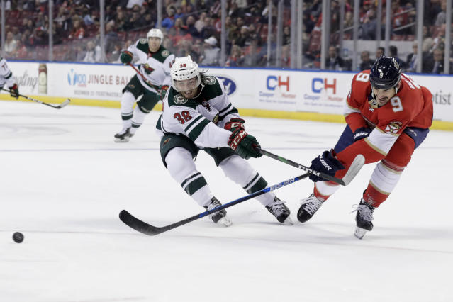 Minnesota Wild right wing Ryan Hartman (38) and Florida Panthers center Brian Boyle (9) chase the puck during the second period of an NHL hockey game, Tuesday, Dec. 3, 2019, in Sunrise, Fla. (AP Photo/Lynne Sladky)
